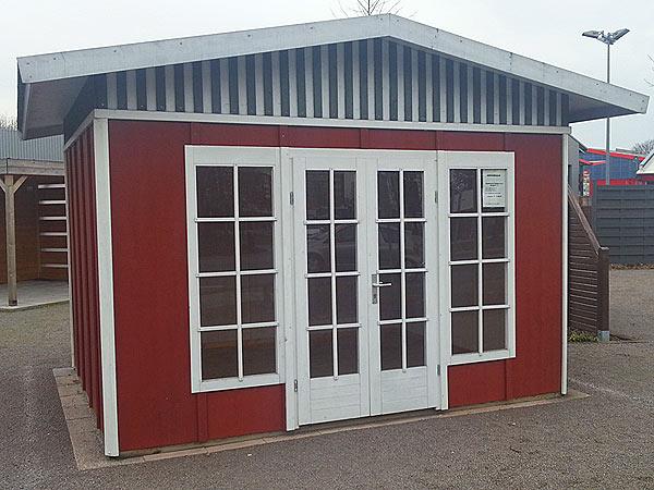 Modernes polnisches Gartenhaus mit weisser eingangstüre und roten wänden